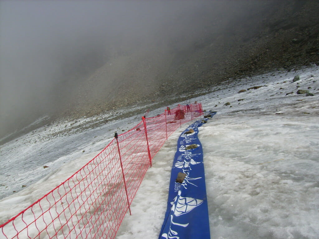 Anyone for a magic carpet ride? Race organizers kept the route slide-free by adding a textile fabric and fencing on a steep section of the glacier. Photo courtesy of Fabian Manceau.